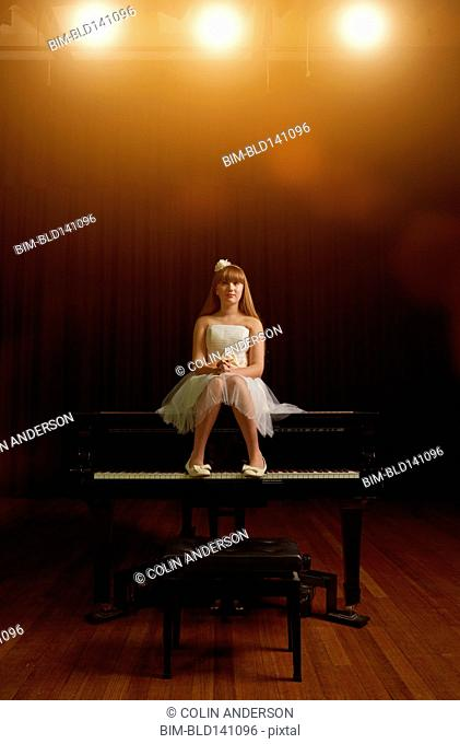Caucasian girl sitting on piano on stage
