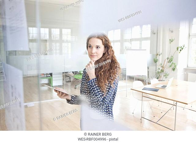 Woman in office looking at papers at glass pane
