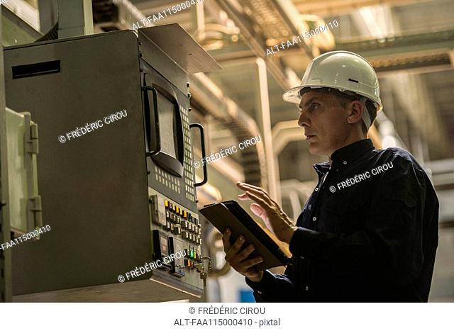 Factory worker using digital tablet in factory