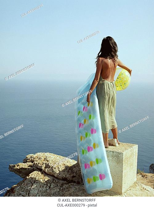 Woman standing on rock over looking the sea holding a beach ball and a lilo
