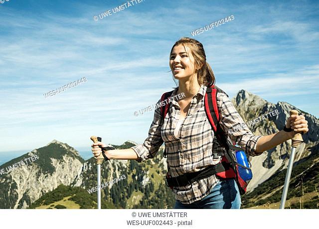 Austria, Tyrol, Tannheimer Tal, smiling young woman on hiking trip