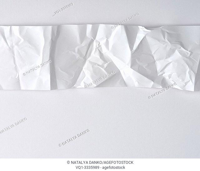 crumpled white strip of paper on a white background, copy space