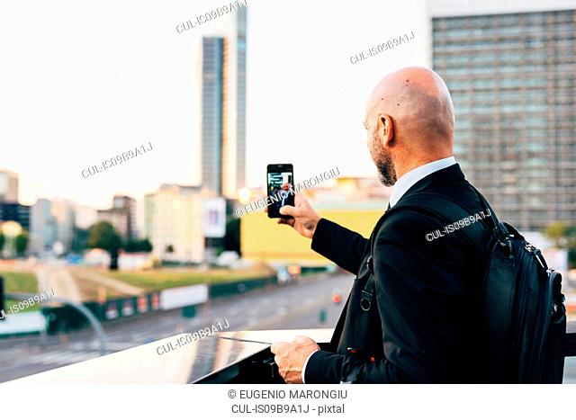 Mature businessman standing outdoors, taking selfie, using smartphone