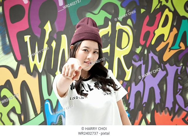 Portrait of young woman in hip-hop style pointing to front against graffiti art