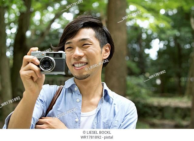 A man in a Kyoto park holding a camera, taking a picture
