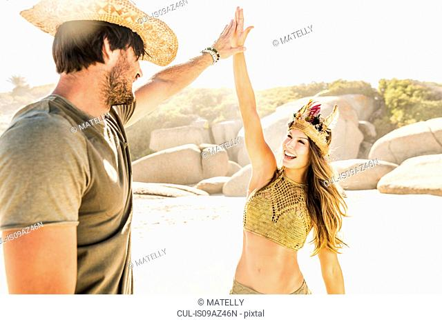 Mid adult couple wearing straw hat and feather headdress highfiving on beach, Cape Town, South Africa