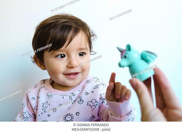 Portrait of smiling baby girl looking at unicorn figure