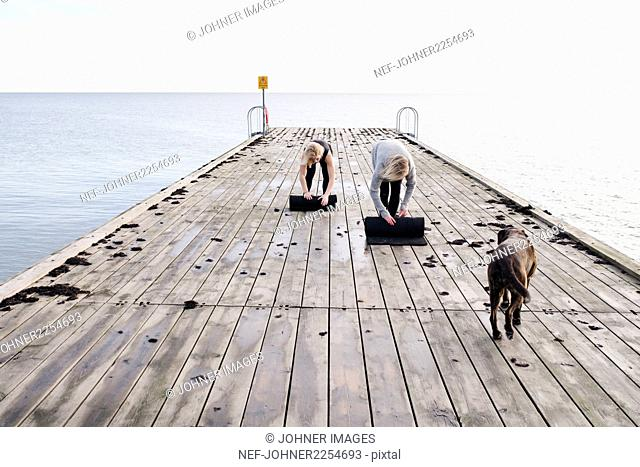 Women rolling up exercise mats on pier