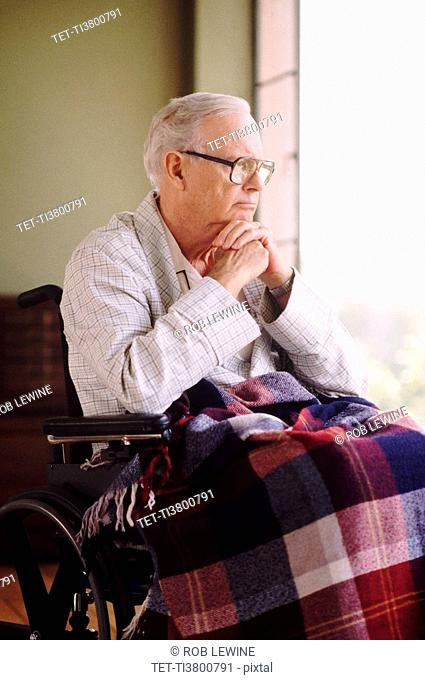 Elderly man sitting in wheelchair while gazing out window