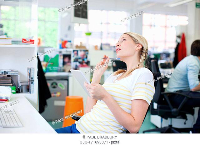 Smiling businesswoman holding notepad and looking up in office