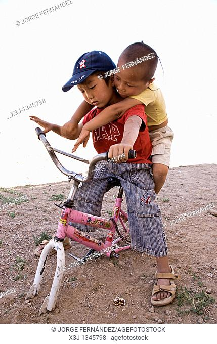 Kids playing with ruined bicycle, Gobi desert, Mongolia