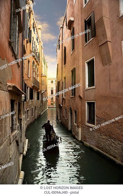 Silhouetted gondolier on narrow canal, Venice, Veneto, Italy