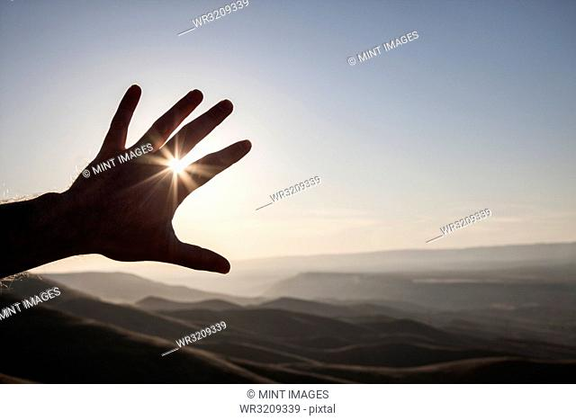 A silhouette of a person's hand in the sun with a landscape of eastern Washington State, USA in the background
