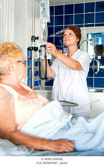 Nurse adjusting patient's intravenous drip