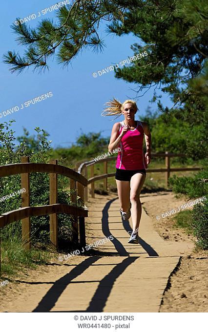 A jogger running along a beachside boardwalk