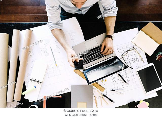 Man using laptop next to construction plan at desk, top view