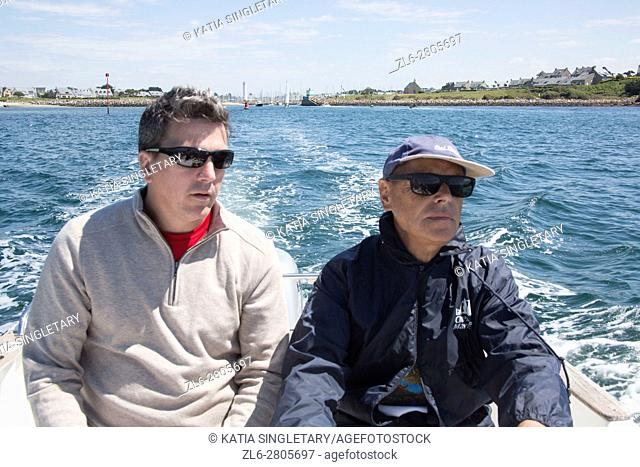Father in law and son having a guy time on a outing on the boat in the ocean, in Brittany, France