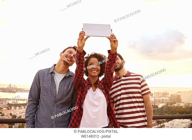 Three good friends taking a selfie on a tablet while standing on a bridge overlooking a city, wearing casual clothing