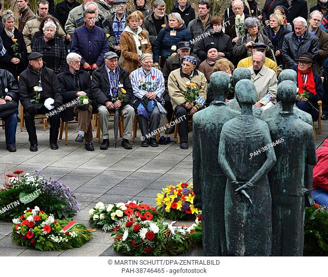 Former detainees and visitors sit in front of the memorial at the former crematorium during a commemoration ceremony at the former National Socialist...