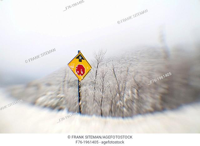 Distorted and blurred lensbaby photograph of a roadsign in snow warning of a coming stop sign ahead
