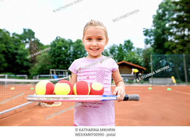 Little girl, lerning to play tennis, balancing balls on a racket