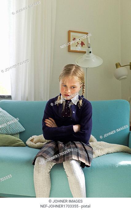 Angry girl sitting on sofa