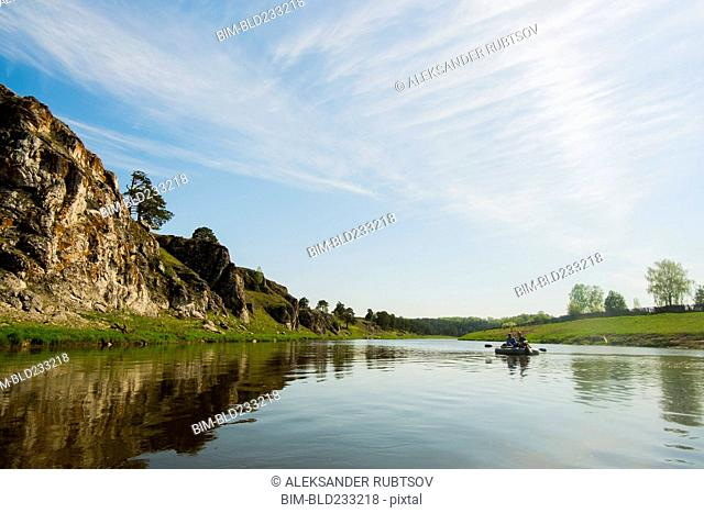 Caucasian men in inflatable raft on river