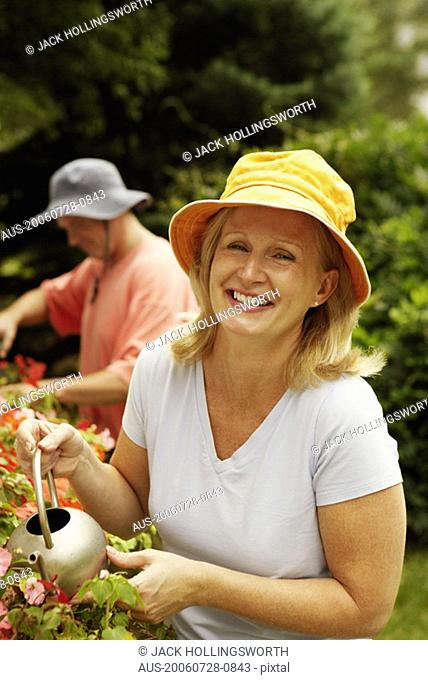 Portrait of a mature woman watering plants and smiling