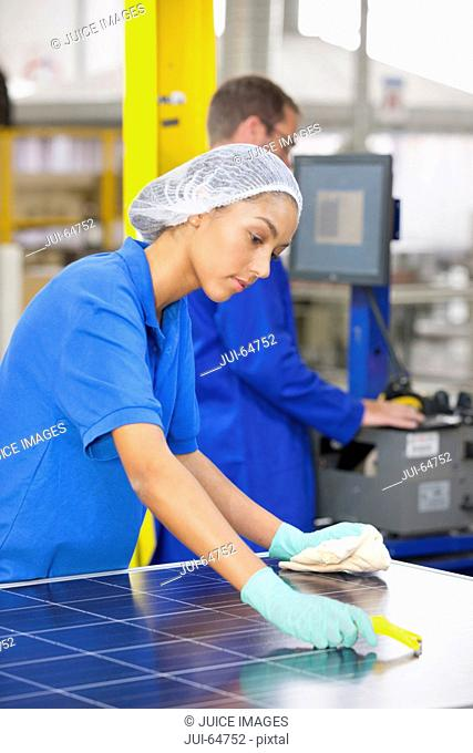 Technician worker cleaning and checking newly manufactured solar panels on production line