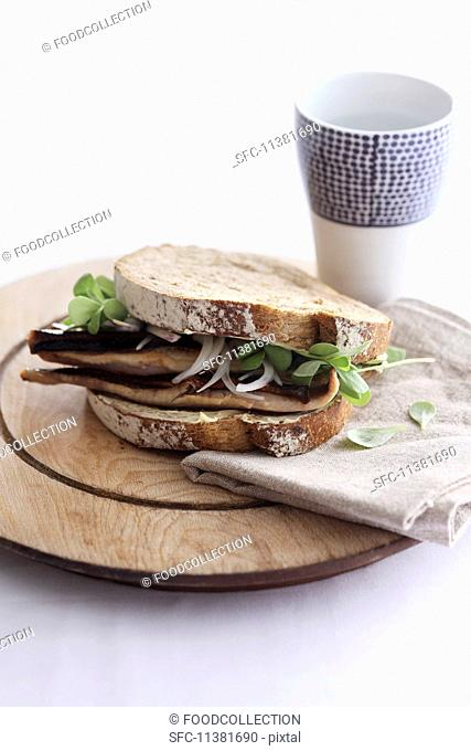 A sandwich with herring, bacon, onions and purslane