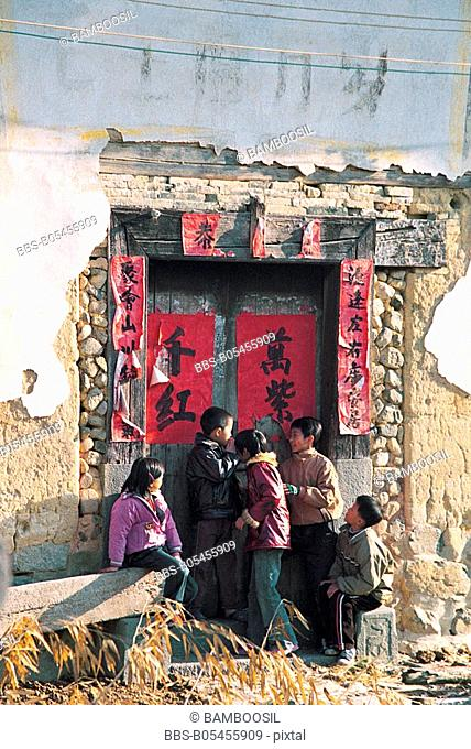 Children playing in front of Yuchange Earth Tower, Nanjing County, Zhangzhou City, Fujian Province, People's Republic of China