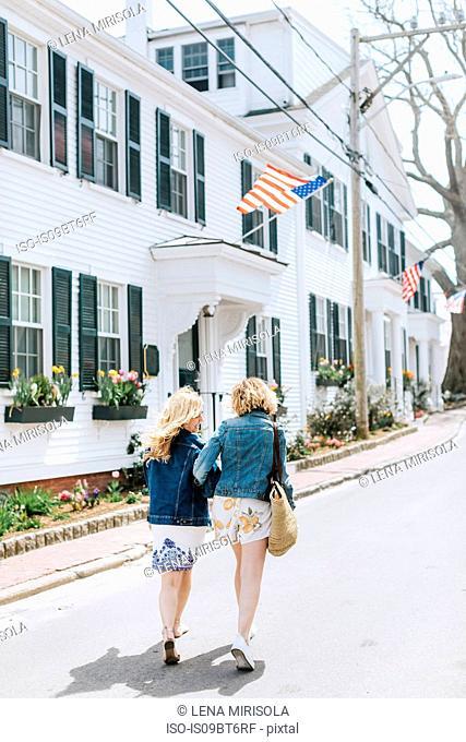 Two young female friends strolling along village road, rear view, Menemsha, Martha's Vineyard, Massachusetts, USA
