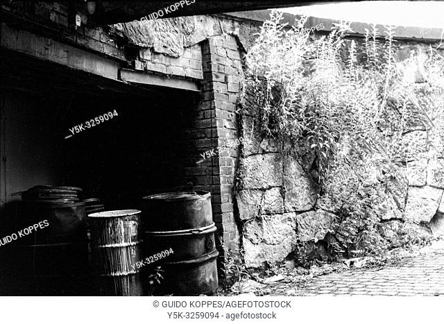 Chemnitz, former Karl Marx Stadt, East Germany. Old and decomissioned oil drums, stached away in a driveway for collection inside the former DDR town