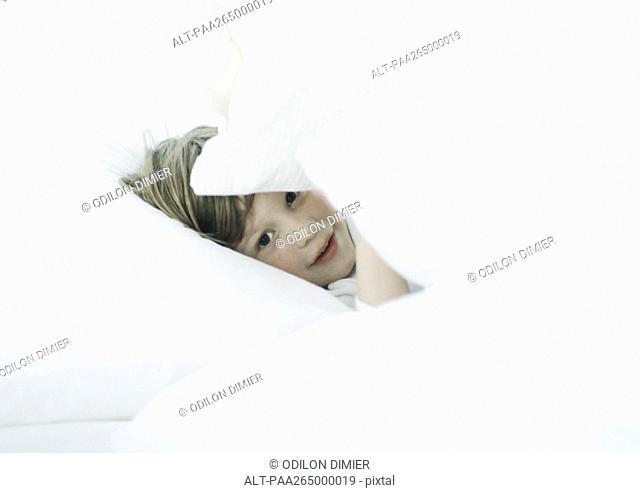Little boy in bed, looking through pillows