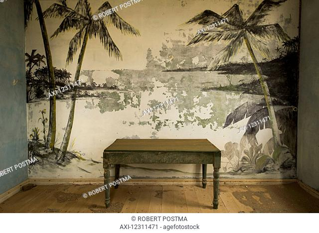 An old table in front of painted palm trees in an abandoned house; Elizabeth Bay, Namibia