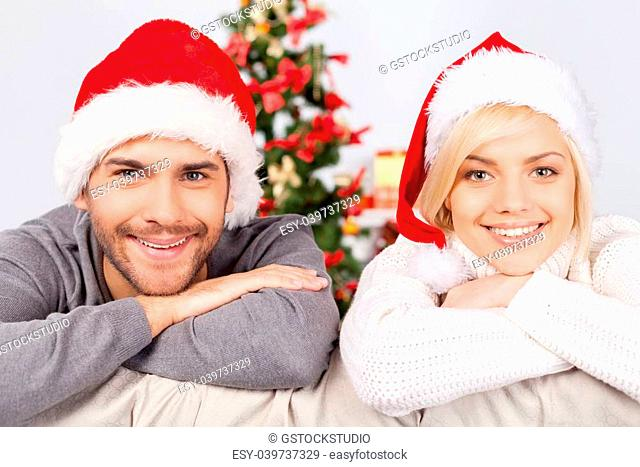 Celebrating Christmas together. Cheerful young couple sitting on the couch and smiling at camera