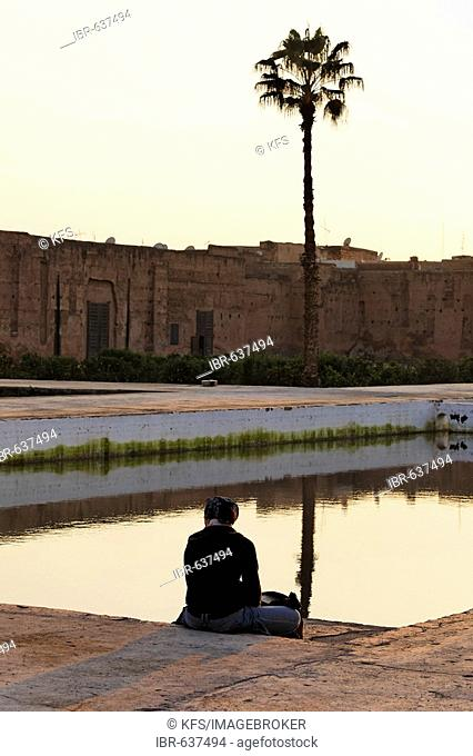 Female tourist resting at the edge of a water basin, historic inner courtyard of Palais EL Badi, Marrakech, Morocco, Africa