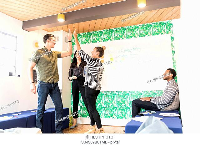 Young businessmen and women high fiving in creative meeting room