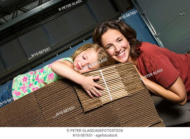 Mother and her young daughter posing together on a pile of cardboard boxes in a factory