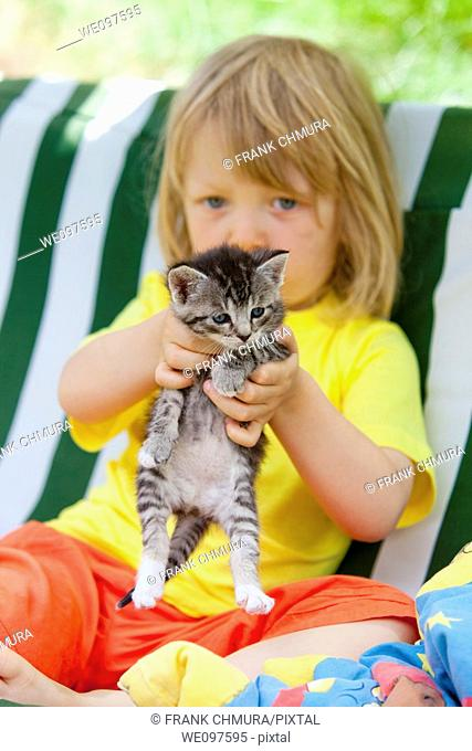blond boy playing with kitten