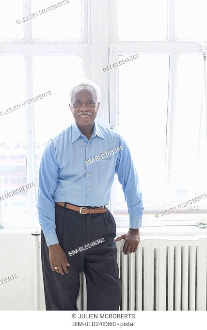 Smiling older Black man leaning on radiator near window
