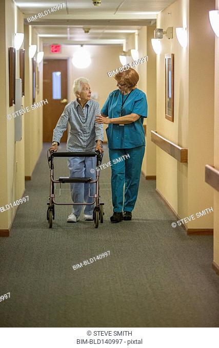 Older Caucasian woman walking with nurse in nursing home