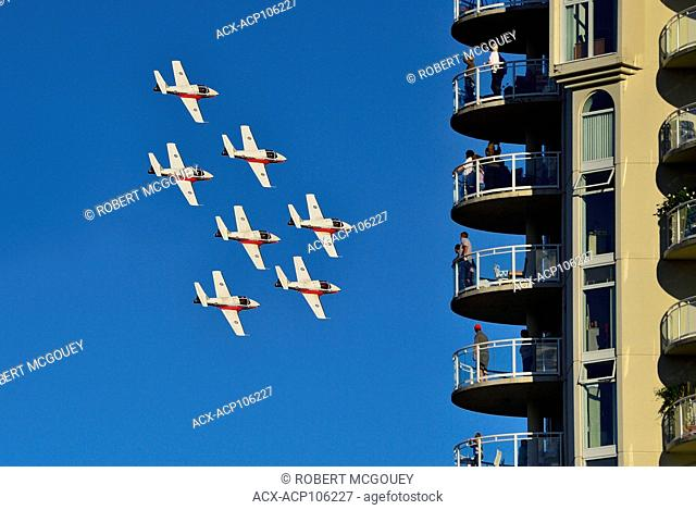 Canadian Forces Snowbirds Squadron 431 flying in formation past a tall condo complex on the harbor in Nanaimo on Vancouver Island, British Columbia, Canada
