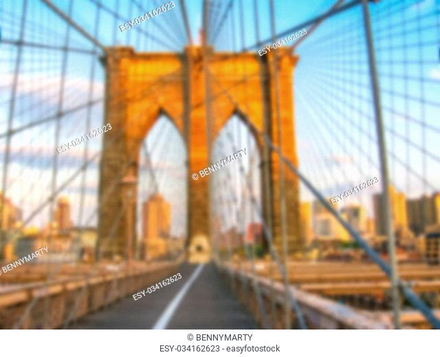 Defocused background of Brooklyn Bridge at sunset in New York, United States. Intentionally blurred post production for bokeh effect
