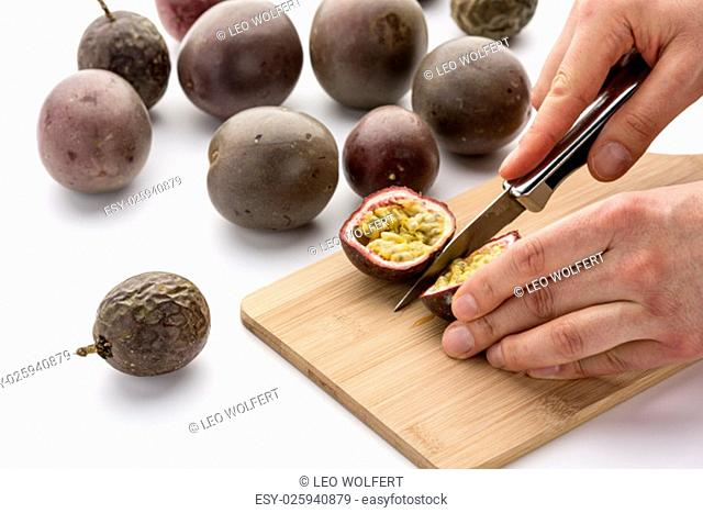 Hands guiding a kitchen knife to cut a juicy passion fruit in halves. Finger tips of a chef are positioning the fruit on a bamboo board