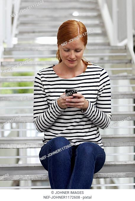 Portrait of young redhead woman sending text messages