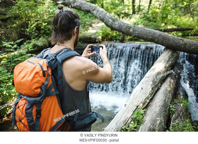 Young man taking a cell phone picture at a waterfall in forest