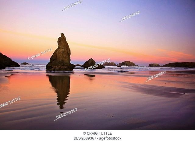 Sunset over rock formations reflecting in tide pools at low tide, bandon beach, oregon, united states of america
