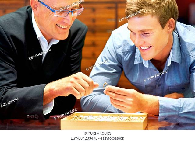 Friendly jeweller helping a young man choose an engagement ring