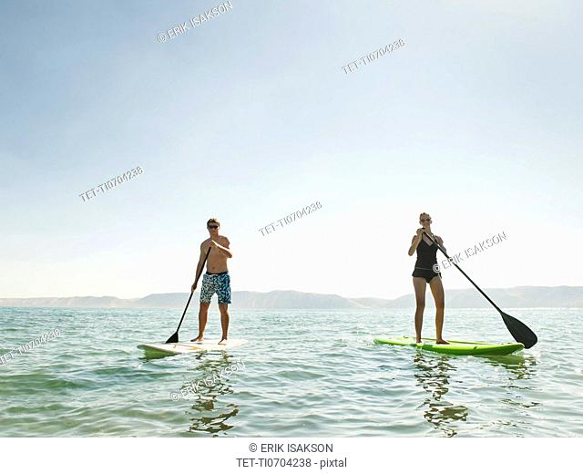 Two people standing on paddleboard